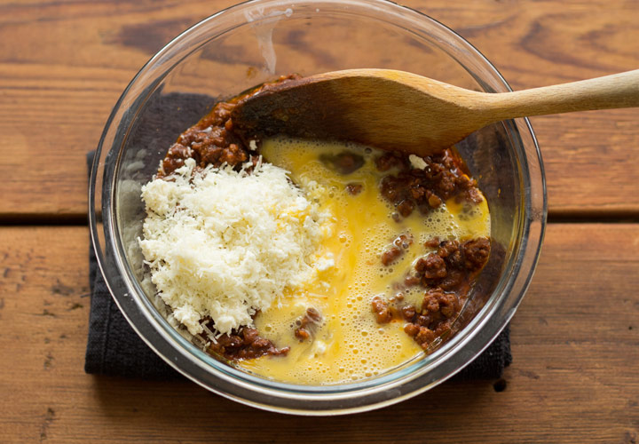 Mixing meat sauce with cheese and egg for pastitsio