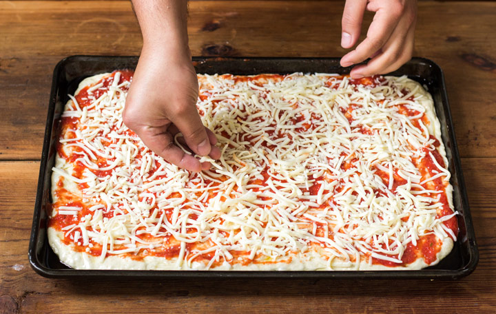 Sprinkle the cheese on top of the Sicilian Pan Pizza