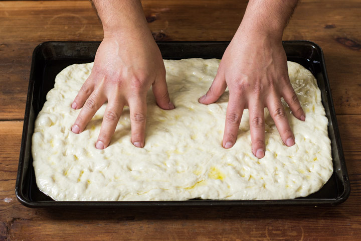 Stretch the dough for Sicilian Pan Pizza using your hands