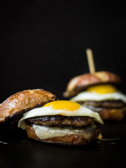 Hot Cross Buns French Toast Breakfast Sandwich - batter and griddle leftover hot cross buns like French toast then top with cheese, sausage, and a fried egg for the best breakfast sandwich ever.